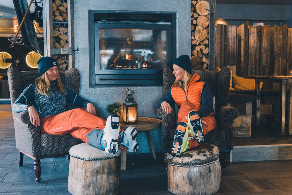 Two girls enjoying hot chocolate in skigear